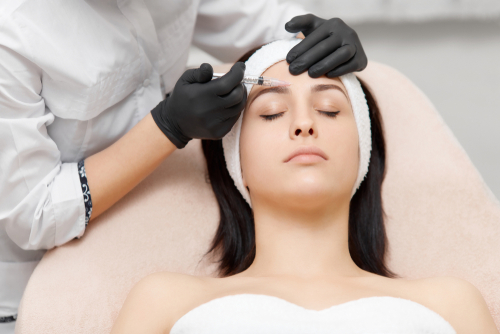 Image of female patient with doctor injecting into her forehead.