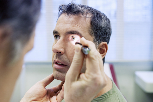 Image of Doctor Shining Light in Middle-Aged Man's Eye