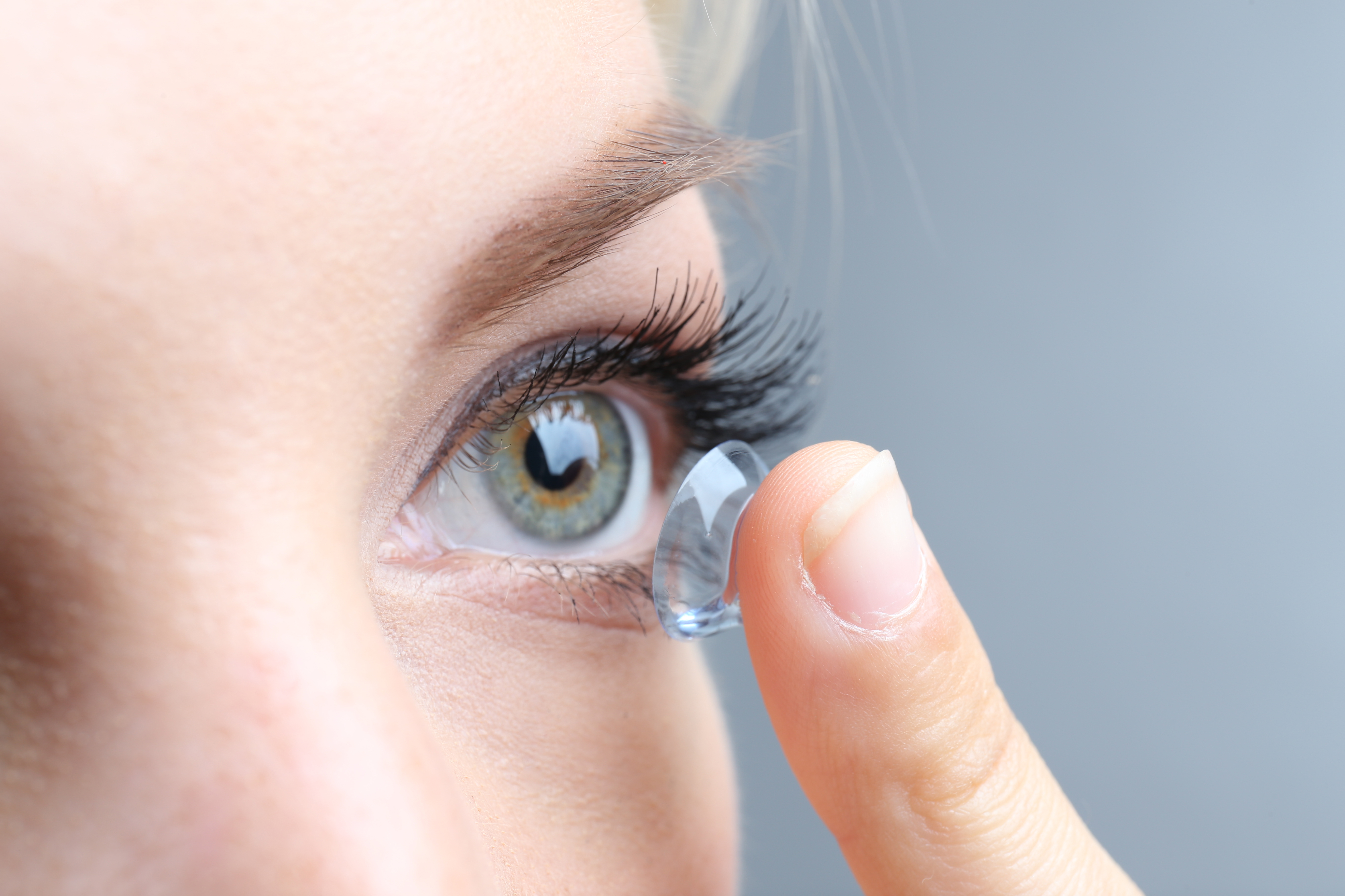 close up on women placing a contact lens in her eye