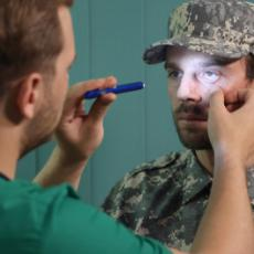 Image of Doctor shining light in man who is dressed in military uniforms's eye.