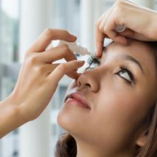 Asian Woman Putting Eye Drops in Her Right Eye