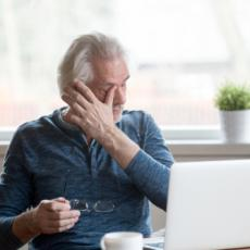 Image of older man in front of computer rubbing his eyes.