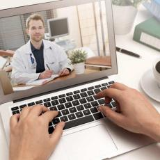 Male doctor on consulting patient through video chat on a laptop computer