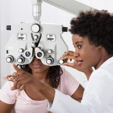 Optometrists uses vision device to test patient's eye sight.