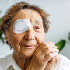 Elderly person wears an eye patch over their right eye post surgery